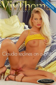 Claudia reclines on a bed